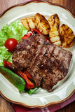 Portions of grilled beef steak with grilled potatoes and paprika Royalty Free Stock Photos