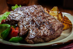 Portions of grilled beef steak with grilled potatoes and paprika Stock Photography