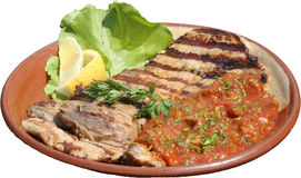 Portions of grilled steak served with tomato sauce and roast vegetables Stock Photography