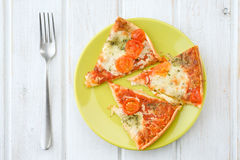 Portions of pizza with cheese and tomato on green plate on wood Royalty Free Stock Photos