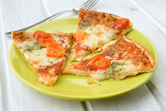 Portions of pizza with cheese and tomato on green plate on wood Royalty Free Stock Photo
