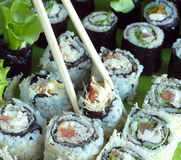 Portions of sushi rolls with salad and ingredients Stock Photography