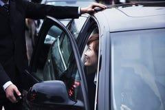 Portière de voiture d'ouverture d'homme d'affaires pour la femme d'affaires au cours de la journée dans Pékin Photo stock