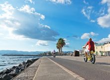 People along the Portixol promenade. PORTIXOL, MALLORCA, BALEARIC ISLANDS, SPAIN - SEPTEMBER 27, 2017: People out and about along the promenade on a sunny day on Stock Image