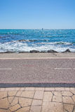 Portixol seaside bicycle route. Seaside bicycle route, boardwalk, waves, turquoise water horizon and ship on the horizon in Mallorca, Balearic islands, Spain Royalty Free Stock Photo
