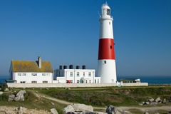 Portland Bill Lighthouse. Portland Bill is a narrow promontory (or bill) of Portland stone, which forms the most southerly part of Isle of Portland, and the Royalty Free Stock Photo