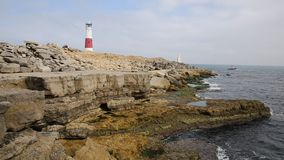 Portland Bill Lighthouse Dorset England UK with boat sailing by coast stock video