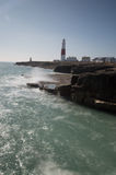 Portland Bill Lighthouse, Dorset. With the waves crashing against the shore Stock Photo
