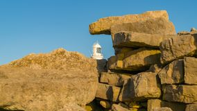 Portland Bill Lighthouse, Jurassic Coast, Dorset, UK. Portland Bill Lighthouse seen through the rocks near Pulpit Rock, Jurassic Coast, Dorset, UK Royalty Free Stock Photos
