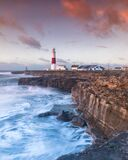 Portland Bill lighthouse in Portland, Dorset, UK with the colors of sunrise