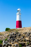 Portland Bill Lighthouse on Portland rocks in sunny summer day Stock Photo