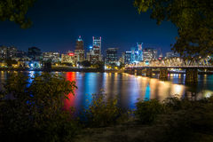 Portland city skyline during early night. With Hawthorne bridge crossing the Willamette River and bushes and trees on the river side Stock Image
