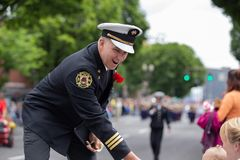 Portland fire and rescue officer handing stickers to onlooker children. Portland, OR / USA - June 11 2016: Grand floral parade. Portland fire and rescue officer royalty free stock photography