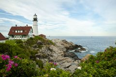 Portland Head Lighthouse Surrounded by Beach Roses in Maaine. Portland Head lighthouse surrounded by rocks, ocean, and beach roses on a warm summer day in Maine Stock Image