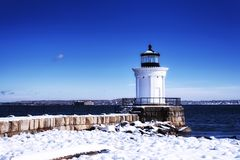 Portland Maine Breakwater Lighthouse winter scene. The Portland Maine Breakwater Lighthouse, also called the Bug Light, on a small jetty covered in snow on a royalty free stock images