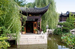 Portland, Oregon: Chinese Classical Garden. Graceful pavilion with flying eave roof and marble terrace flanked by graceful weeping willow trees overlooks the Stock Image