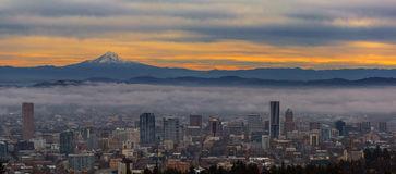 Portland Oregon Cityscape and Mount Hood at Sunrise. Foggy Portland Oregon downtown cityscape and Mount Hood during sunrise panorama royalty free stock images