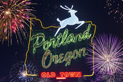 Portland, Oregon sign with deer and flashing fireworks on the sky in the background. Sign in Portland, Oregon with jumping deer and image of oregon's borders Royalty Free Stock Photo