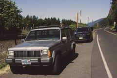 Portland Oregon, USA - Juni 12, 2015: Gamla och nya Jeep Cherokee som parkeras på vägen Royaltyfri Bild