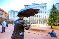 Allow Me, also known as Umbrella Man, is an iconic 1983 bronze s. Portland, United States - Dec 19, 2017 : Allow Me, also known as Umbrella Man, is an iconic stock photos