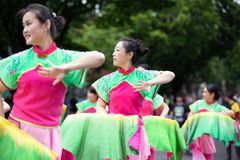 Asian ladies in traditional costume dancing on the street. stock photo