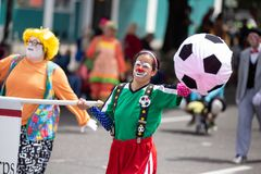 Clown carrying a soccer ball royalty free stock photography