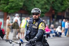 Cop on a bicycle wearing helmet royalty free stock image