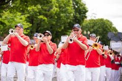 Marching band with tubas at the event. Portland, OR / USA - June 11 2016: Grand floral parade - Male marching band dressed in Standard TV and appliance uniform royalty free stock photography