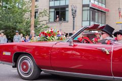 People driving old vintage red Cadillac down the street stock image