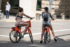 Two young attractive females on bikes royalty free stock photo