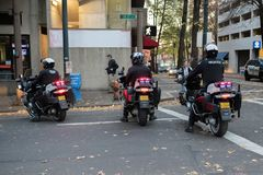 Three police officers on the motorcycles blocking the street royalty free stock image