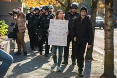 Female protester surrounded by cops royalty free stock photos