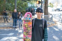Teenager with skateboard crossing the street royalty free stock photo