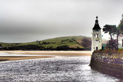 Portmerion by the sea. The tower by the sea at Portmerion, North Wales, with the sandbanks visible as the tide rises, with a green hill in the background, with Royalty Free Stock Photo