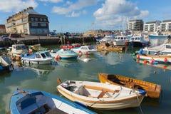 Porto ad ovest Dorset della baia con le barche su un cielo blu e su un mare calmi di giorno di estate Immagini Stock