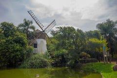 PORTO ALEGRE, BRASILIEN - 6. MAI 2016: nett und altes windmilllocated nah an einem kleinen See mit Tieren Stockfotografie