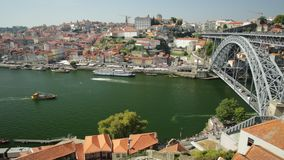 Porto Bridge time lapse. Picturesque urban landscape with tourist boats cruising under Douro River. Aerial view time lapse of Dom Luis I Bridge, Ribeira stock video