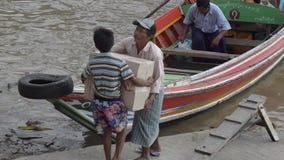 PORTO, CAIS & MOLHE: ÁSIA - a criança traz a caixa dos bens ao barco de espera video estoque
