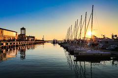 Porto commerciale degli yacht, del motore e delle barche a vela in mare al tramonto Immagini Stock