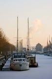 Porto congelado com os navios no inverno no por do sol fotografia de stock royalty free