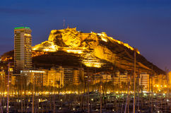 Porto contro il castello nella notte Alicante, Spagna Immagine Stock