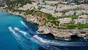 Porto Cristo, Majorca, Spain. Top aerial view of the resort Blau Punta Reina and watercraft that speed up on the sea. Summer time stock footage