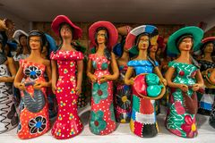Porto de Galinhas beach, Ipojuca, Pernambuco, Brazil - September, 2018: Colorful little clay woman sculptures painted with vibrant stock photography