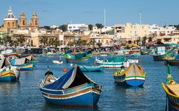 Porto de Marsaxlokk com os barcos tradicionais, coloridos de Luzzu na baía com mercado do fundo imagens de stock royalty free