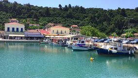 Porto do porto de Grécia - de Katakolon com os restaurantes locais dos barcos de pesca e águas efervescentes do oceano video estoque