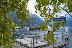 Porto do lago em Suíça com as lanternas de madeira brancas dos estaleiros e as bandeiras vermelhas foto de stock royalty free