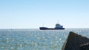 Porto entrando do navio de carga geral e navigação perto das pedras do quebra-mar filme