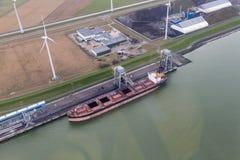 Porto holandês Eemshaven com turbinas eólicas e e cargueiro que transporta carvões imagens de stock royalty free