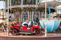 Porto Honfleur de Caroussel com a menina bonita no carro vermelho Fotos de Stock Royalty Free