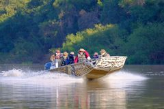 PORTO JOFRE, MATO GROSSO, BRAZIL, JULY 27, 2018: Tourists and guide on boat tour for Jaguar wildlife watching, Pantanal. PORTO JOFRE, MATO GROSSO, BRAZIL, JULY stock photography